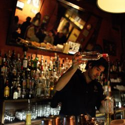 Photograph of a barman making a cocktail in a bar in Milan.
