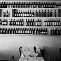 An almost black and white photograph of wine bottles in a restaurant in Milan.