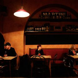 Photograph of people at separate tables in a bar in Milan.