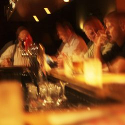Blurred photograph of the inside of a bar with what looks like a difficult conversation going on.
