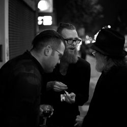 Black and white photograph of two men outside a bar, one of them seems to be telling an amazing story.