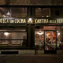 Night time photograph of the outside of a bar in Milan.
