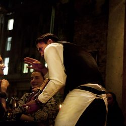Photograph of a waiter entrancing a young women in his apparent description of a bottle of wine.