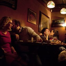 Photograph of a girl kissing a man in a bar with other people sat around.