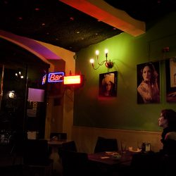 Photograph of a thoughtful looking out of a window into the night in a darkly lit bar.