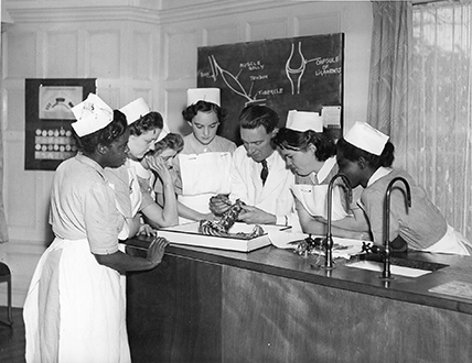 Black and white photograph of nurses in Victoria Hospital School being taught medicine in the 1950's.