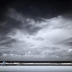 Infrared photograph of a lone rider on Holkham sands with a dramatic sky.
