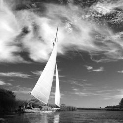 Black and white photograph of sailing yacht on the Norfolk Broads.