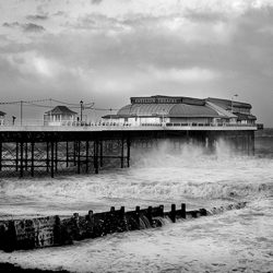 Black and white photograph of Cromer pier in rough seas.