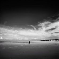 Black and white photograph of a birdwatcher on Wells-next-the-sea sands.