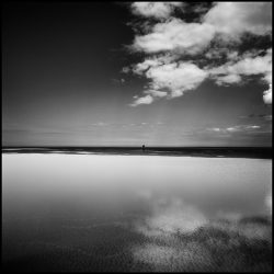 Black and white photograph of clouds reflected in pools of water on Holkham sands Norfolk.