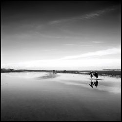 Black and white photograph of two people carrying wellingtons on Holkham sands Norfolk.