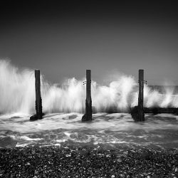 Black and white photograph of waves pounding old wooden sea defences on the Norfolk coast.