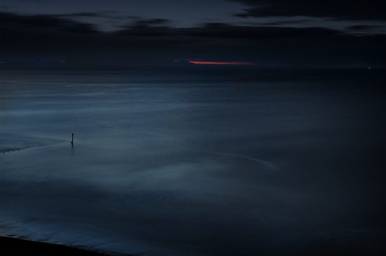 Photograph of the sea at dusk with a red strip of the setting sun on the horizon