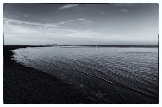 Tri tone photograph of a bleak looking sea shore and people in the far distance