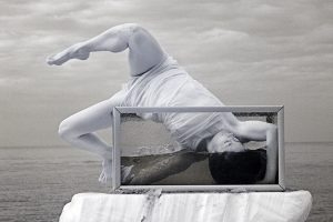Infrared photograph of a girl dancing into an aquarium on Cromer beach.