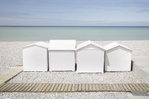 Photograph of white beach huts on the Normandy coast.